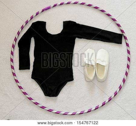 The concept of fitness, diet, weight loss, health body long sleeve leotard or gymnastics, shoes for gymnastics and hula hooping on the bright home background.