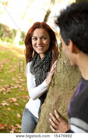 Happy times between a young couple at the park in autumn season (selective focus with shallow DOF)