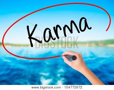 Woman Hand Writing Karma  With A Marker Over Transparent Board
