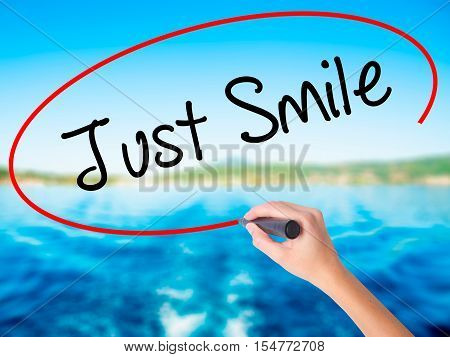 Woman Hand Writing Just Smile With A Marker Over Transparent Board