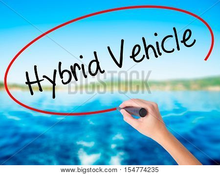 Woman Hand Writing Hybrid Vehicle With A Marker Over Transparent Board