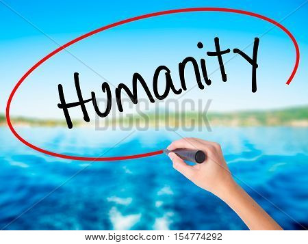 Woman Hand Writing Humanity  With A Marker Over Transparent Board