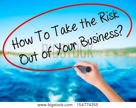 Woman Hand Writing How To Take The Risk Out Of Your Business? With A Marker Over Transparent Board