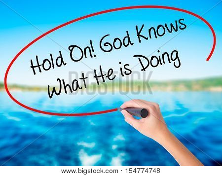 Woman Hand Writing Hold On! God Knows What He Is Doing With A Marker Over Transparent Board