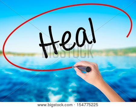 Woman Hand Writing  Heal  With A Marker Over Transparent Board