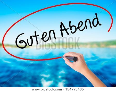 Woman Hand Writing Guten Abend  (good Evening In German) With A Marker Over Transparent Board