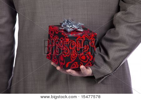 Businessman holding a wrapped Valentine present behind his back