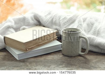 Hot drink with books and plaid on windowsill