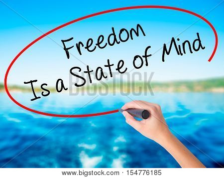 Woman Hand Writing Freedom Is A State Of Mind With A Marker Over Transparent Board