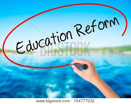 Woman Hand Writing Education Reform With A Marker Over Transparent Board