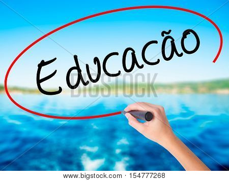 Woman Hand Writing Education (educacao In Portuguese) With A Marker Over Transparent Board