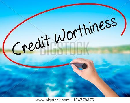 Woman Hand Writing Credit Worthiness With A Marker Over Transparent Board