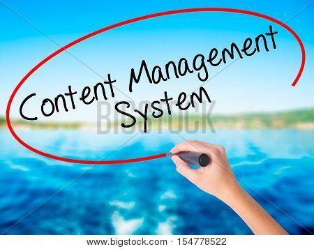 Woman Hand Writing Content Management System  With A Marker Over Transparent Board