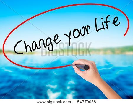 Woman Hand Writing Change Your Life With A Marker Over Transparent Board