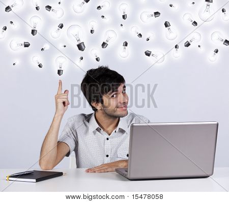 Young man with lots of ideas in the office working with his laptop