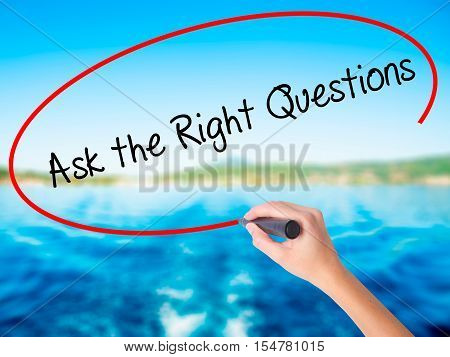 Woman Hand Writing Ask The Right Questions With A Marker Over Transparent Board