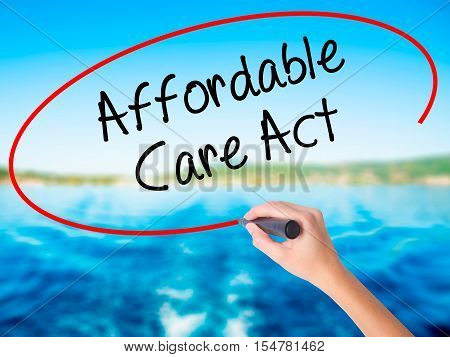 Woman Hand Writing Affordable Care Act With A Marker Over Transparent Board