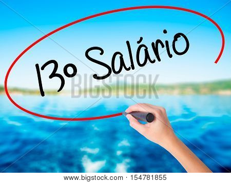 Woman Hand Writing 13 Salary (13O Salario In Portuguese)  With A Marker Over Transparent Board