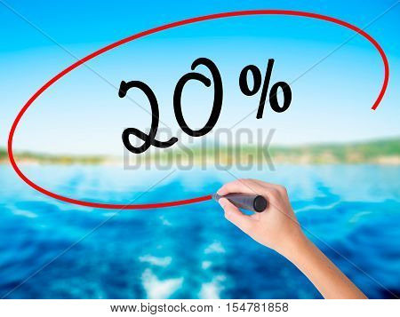Woman Hand Writing 20% With A Marker Over Transparent Board