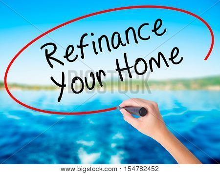 Woman Hand Writing Refinance Your Home With A Marker Over Transparent Board