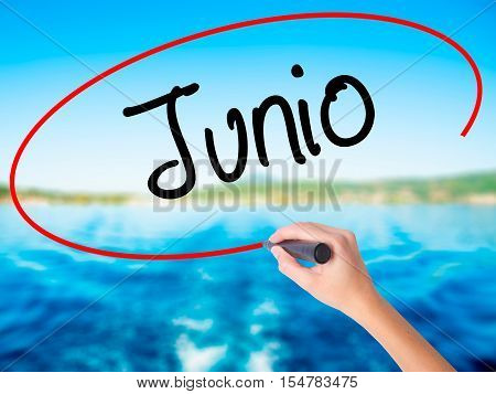 Woman Hand Writing Junio (june In Spanish)   With A Marker Over Transparent Board