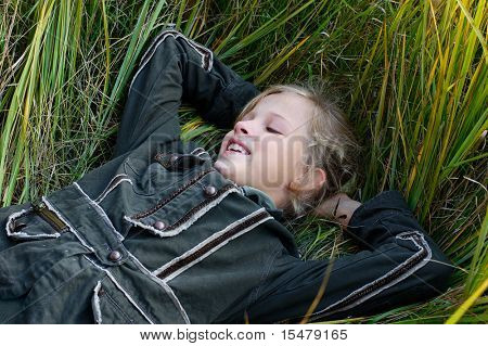 young blond girl lying in the grass and smiling