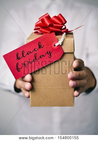 closeup of a young caucasian man in a white shirt holding a gift box with a red label tied to it with the text happy black friday written in it