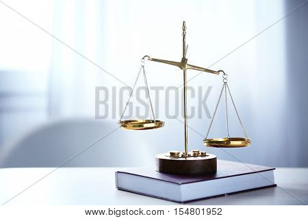 Justice scales and book on table in the room