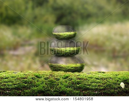 Pyramid of the beautiful volume of stones on the moss. The concept of protection of nature environment stability