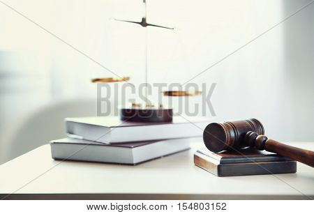 Judges gavel, justice scales and books on table in the room