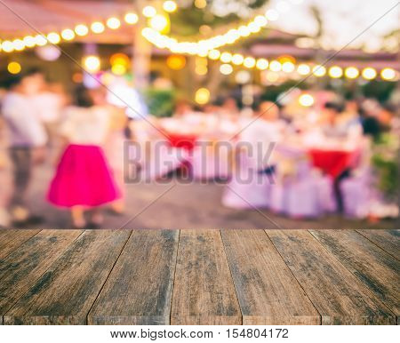 Wood table with blur party background. Abstract blur party background wood table for display your product. Empty wood table and space. Wood board empty table in front of blur party background. Perspective wood table over blur party.