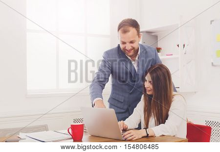 Businessman supervising his assistant's work on the laptop computer. Man helps woman in the office. Male boss and female secretary. Communication of manager and stuff, checking job execution
