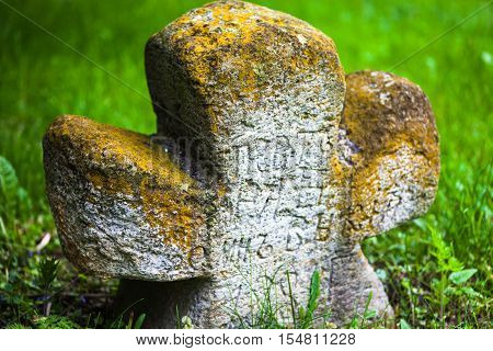 Old moss-grown stone cross with engraved Old Church Slavonic inscriptions. Kyiv Ukraine. Close up.