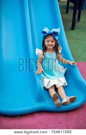 little girl three years with the blue bow on her head slipping with a plastic blue hill at sunset in the summer