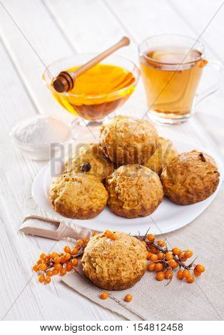 muffins with tea, sea-buckthorn berries and honey on the white wooden background