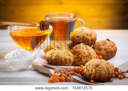 muffins with tea and honey on the white wooden background