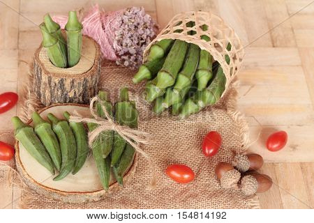 Fresh okra pods and sliced on wood background