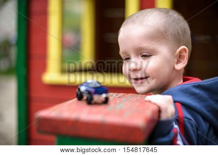 Little Toddler Boy Playing With Car Toy. Selective Focus On Face Of  And . Smiling  Having Fun. Leas