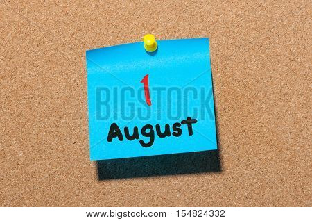 August 1st. Day 1 of month, color sticker calendar on notice board. Summer time. Close up.