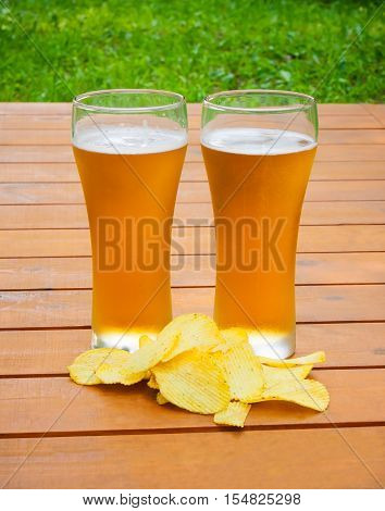 Light beer with potato chips on a wooden table