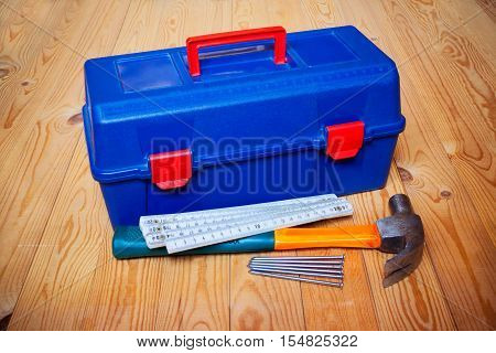 Tools box hammer nails and folding ruler on wooden background
