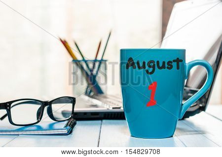 August 1st. Day of the month 1, morning coffee cup with calendar on business workplace background. Summer time. Empty space for text.