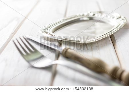 Vintage fork and knife on wooden background