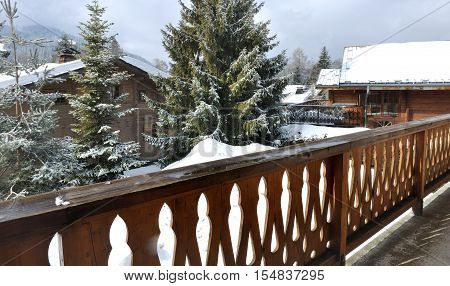 wooden railing balcony of a cottage in a village in winter