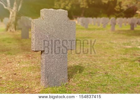 Sunny tomb with stone cross in the cementery