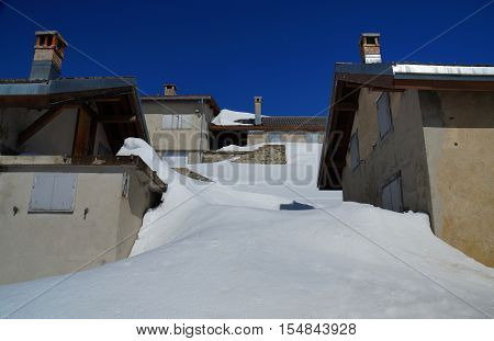 Houses in ski resort made winter-firm at the end of the winter season. Fresh, smooth snowdrifts reach up the second floor and the roof. Oberalppass, Swiss, May 2016