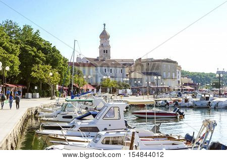 Krk town port Croatian island. View of the harbour boats docked at marina and the bell tower of the Church of the Assumption of Blessed Virgin Mary with an angel holding a trumpet.