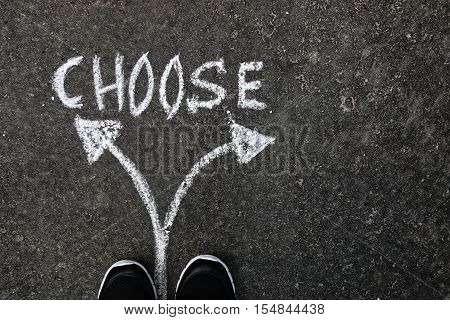 Arrows drawn with chalk on the pavement concept difficult choices composed in life