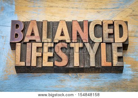 balanced lifestyle - word abstract in vintage letterpress wood type printing blocks against grunge wood