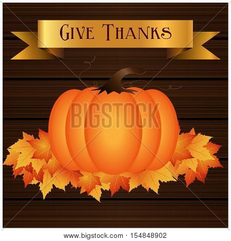 Give thanks background with a dark brown wood texture. Orange pumpkin on top of fall leaves. Gold banner with give thanks verbiage on top